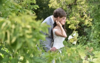 The groom kisses the cheek of his bride while they are entirely surrounded by mother nature.