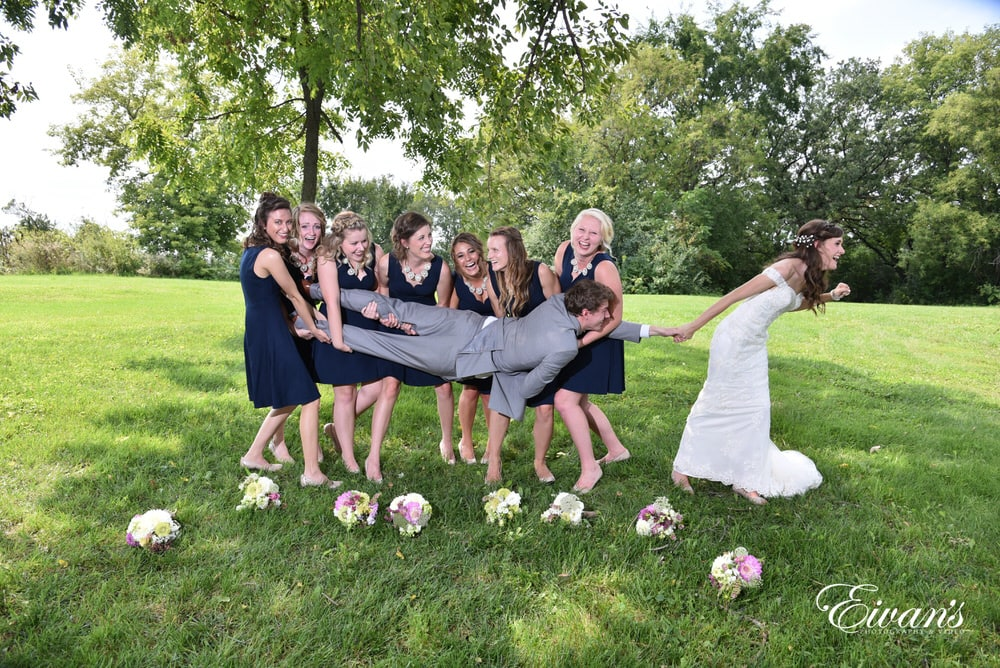 The bridesmaids try to carry the groom while she tugs on his arm trying to keep him near her.