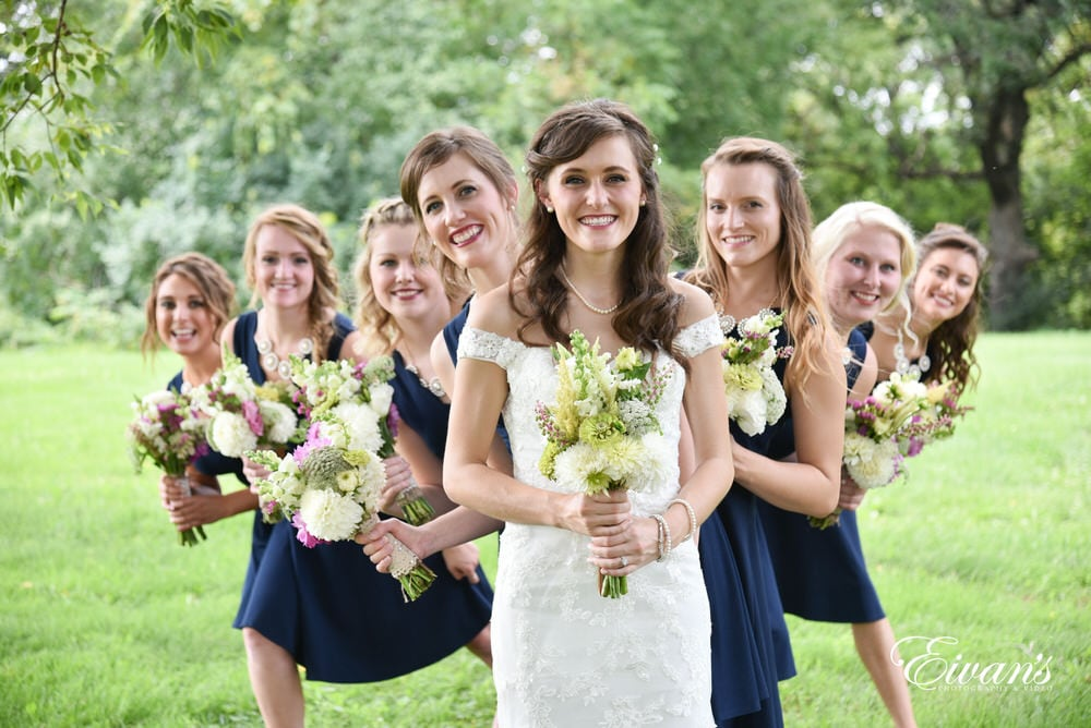 The bride stands with all of her bridesmaids behind her in a moment of happiness as they all back her decision.