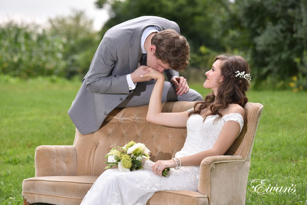 The groom kisses his bride's hand while she lays on a couch in the middle of lush green field.