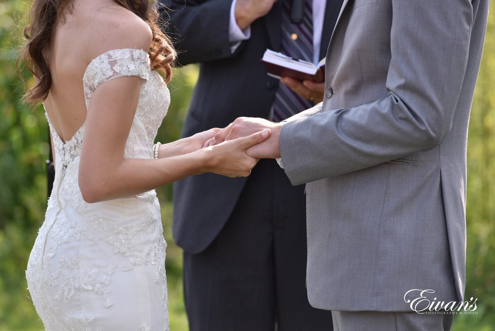 The couple hold hands at the alter in the final moments before they will become one another's forever.