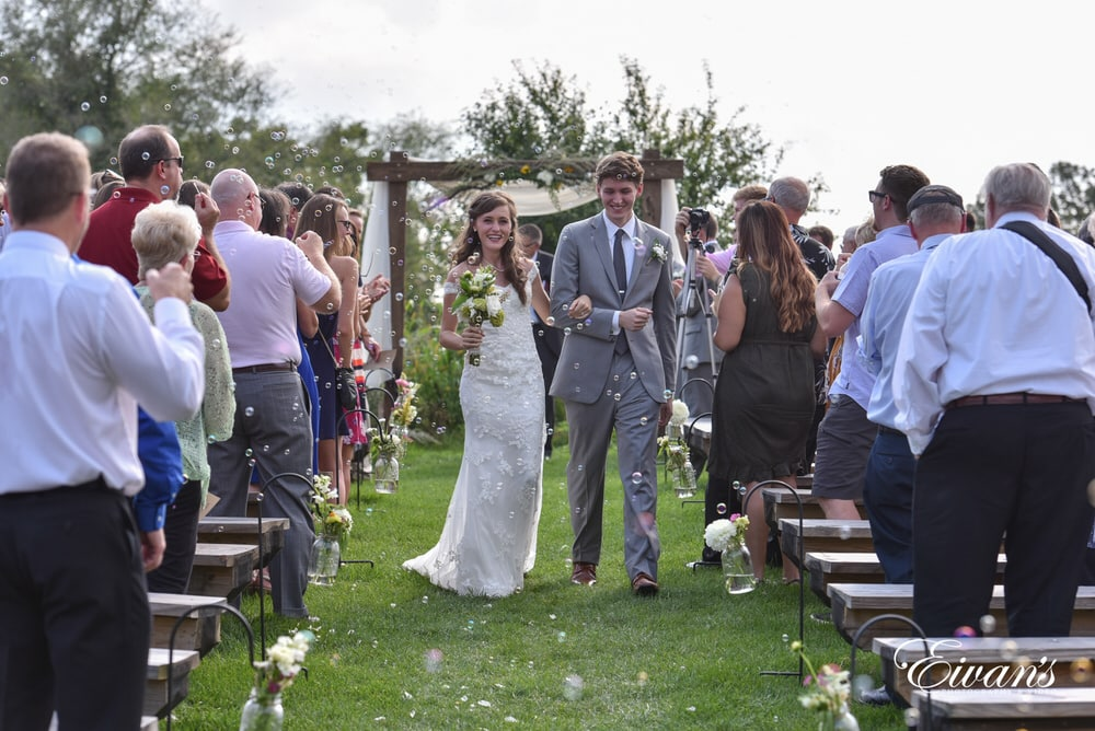 The bride and groom exit the ceremony while their guests blow bubbles at them celebrating this tremendous affair.