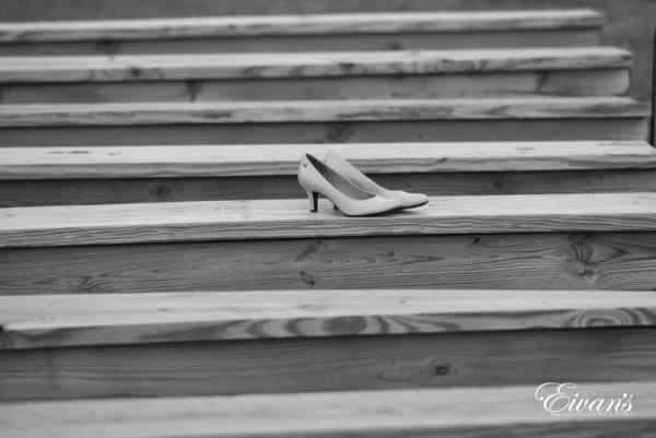 The bride's heels lay upon the rustic wooden benches that the couple's loving friends and family will soon fill.