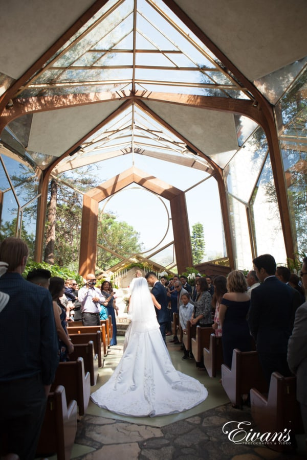 The bride walks down the to the alter to her beloved in a beautiful church with the shining sun.
