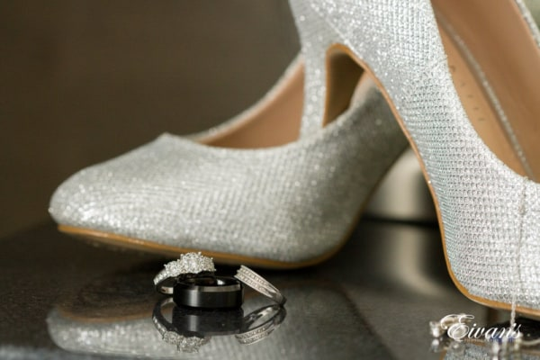 The couple's rings sparkle next to the bride's dazzling silver shoes.