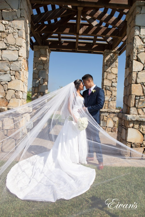 The groom and bride hold one another while theres a long and elegant veil cascading in the wind.