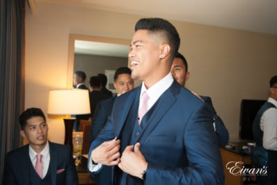 The groom beams with love and happiness as he prepares to his amazing bride.