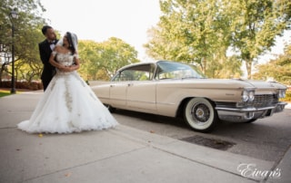 The groom embraces his bride in front of an old 1950's cadillac giving this couple a different edge to their wedding.
