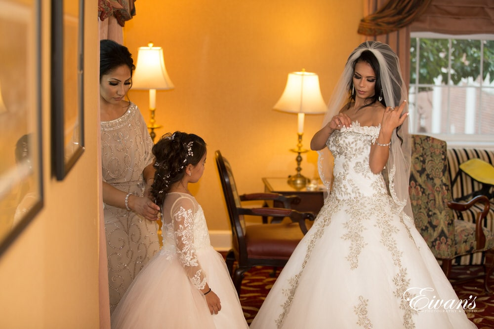 The bride fixes gown while also the bridesmaids and flower girl all prepare for such a tremendous affair.