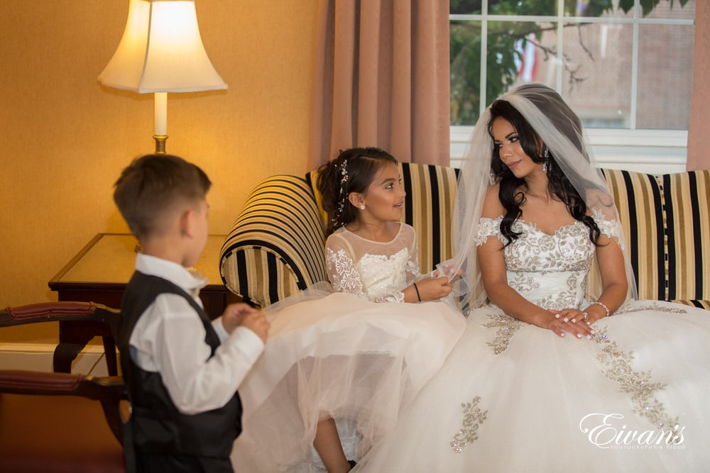The bride sits with the ring bearer and the flower girl all talking before her moment down the isle.
