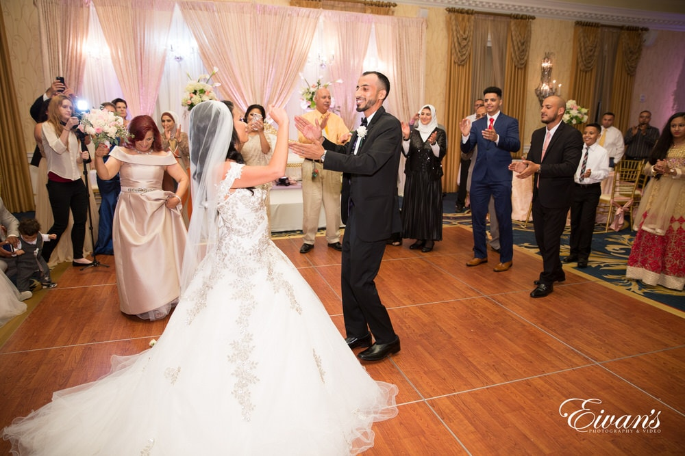 The bride and groom clap as they music gets the enter room filed with happiness and true love.