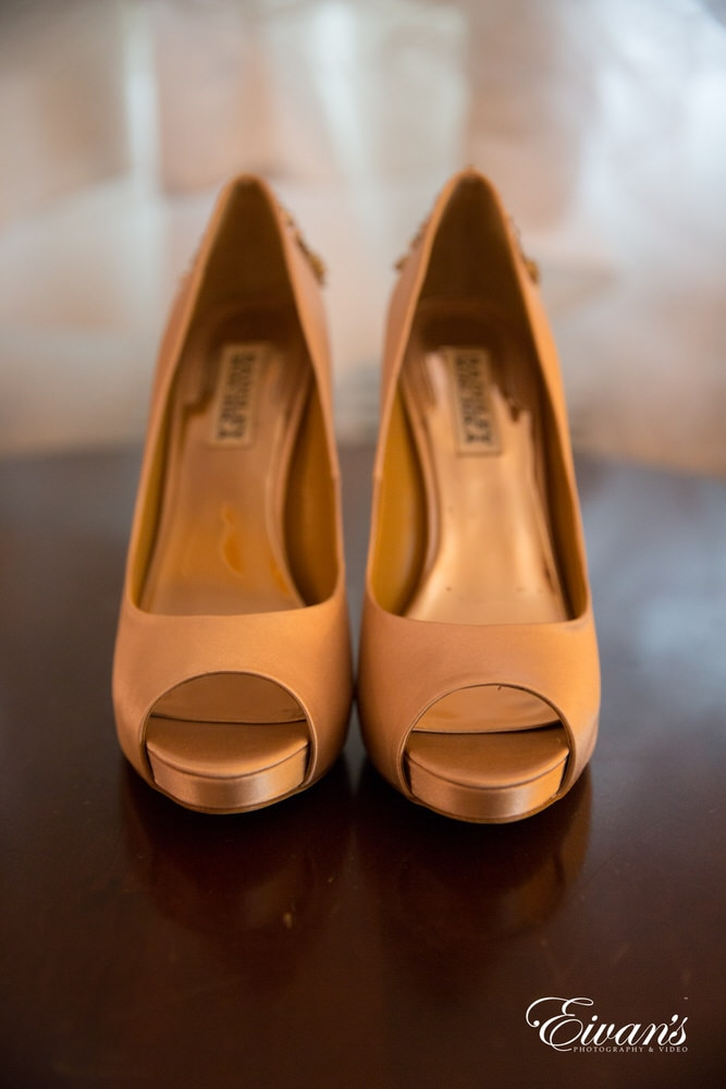The bride's champagne open-toed heels help complement the gold and bronze accents on her dress.