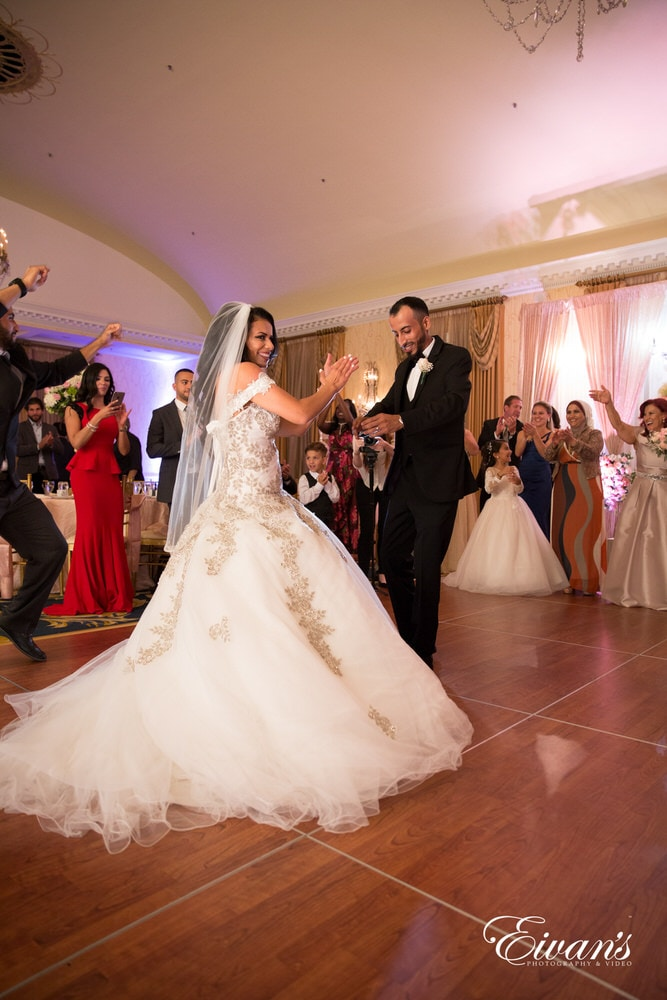 The groom and bride cheer as the entire bridal party join them on the dance floor to celebrate this joyous occasion.