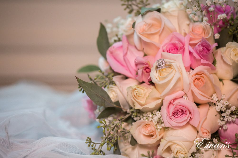 The brides bouquet of white and pink roses is also holding the ring that will soon be placed onto her finger.