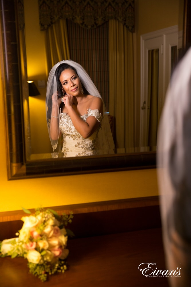 The bride delicately puts on her jewelry waiting for the moment she's able to see the love of her life.