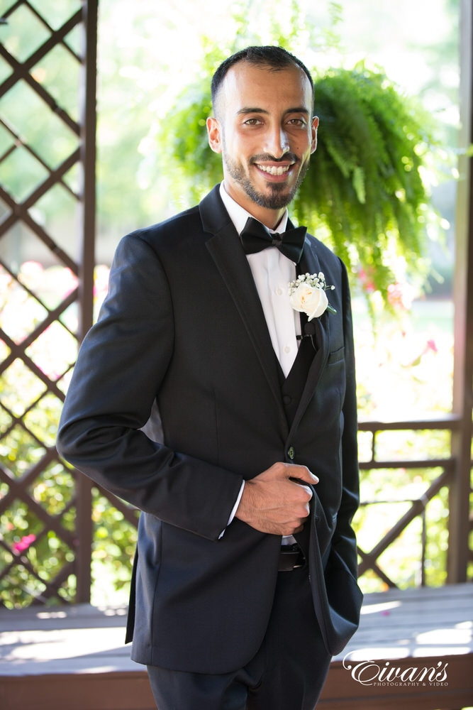 The groom looks very handsome while waiting inside the gazebo for the love of his life.