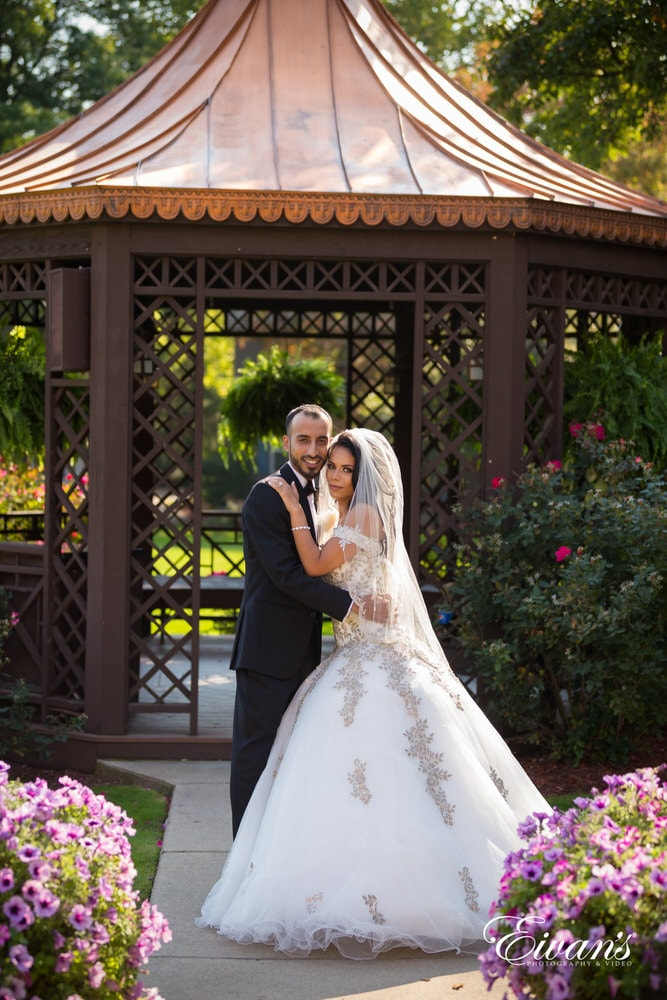 The groom and bride hold one another in their full attire in front of a romantic gazebo.