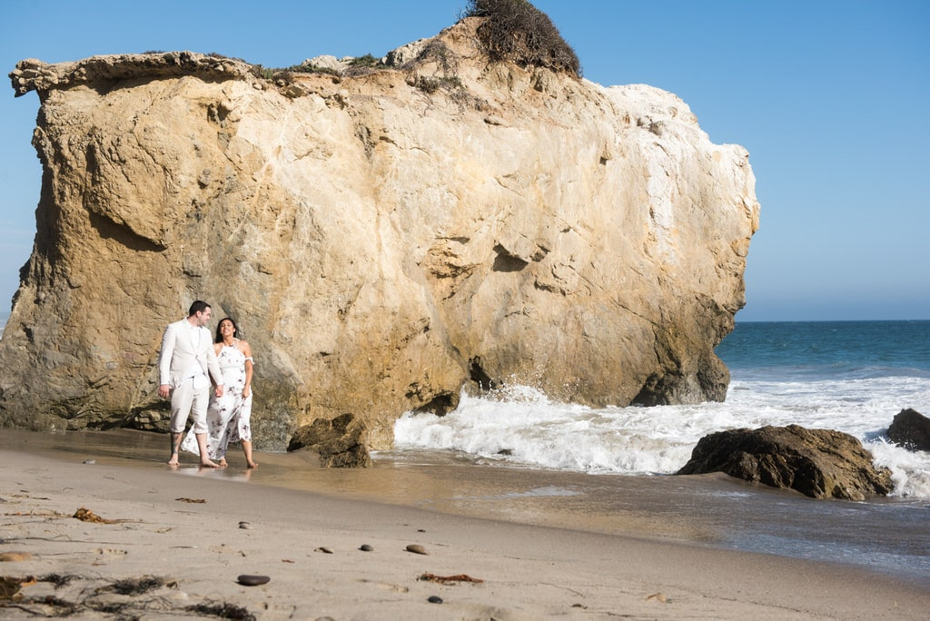 engaged man and woman walking on the beach during the daytime