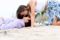 A newly engaged woman playfully hangs her head over her soon-to-be husband as he lies in the sand of the beach.