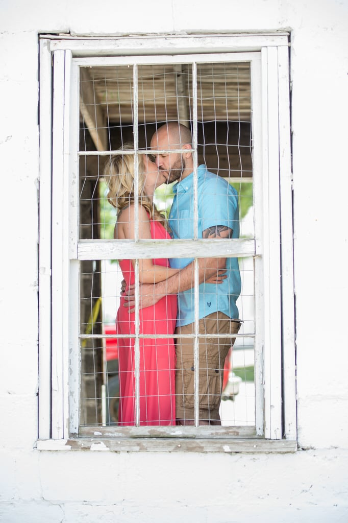 A newly engaged couple share a kiss in the screen window of an old, white barn.