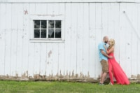 A newly engaged couple looking adoringly at one another in front of an old, rustic barn.