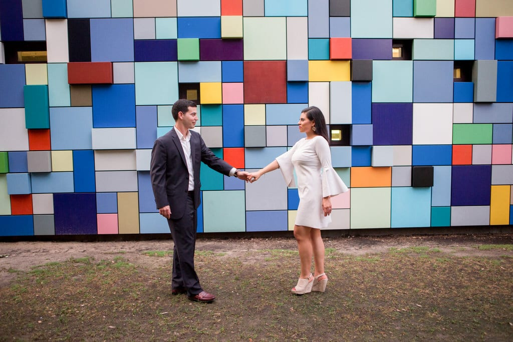 A newly engaged couple stand face to face holding hands in front of a multi-colored, geometric wall.