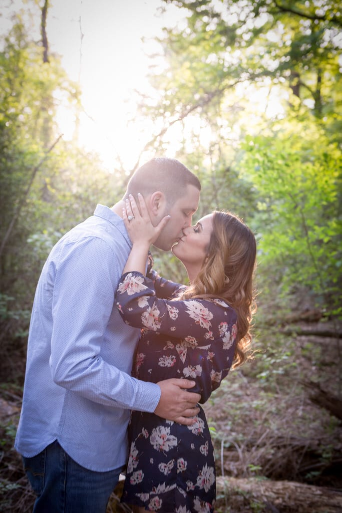 A newly engaged couple kiss each other passionately in the middle of the forest.
