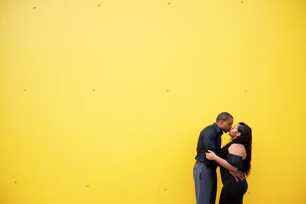 A newly engaged couple, clad in all black, share a kiss in front of a yellow background.