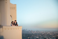 A newly engaged couple admires the city below them as the sun begins to set.