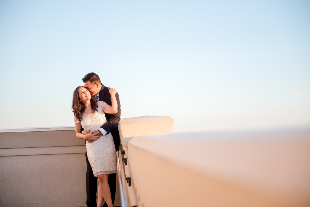 A man embraces his soon-to-be wife on a roof in the late afternoon. He kisses her head, and she smiles widely while grabbing his shoulder.
