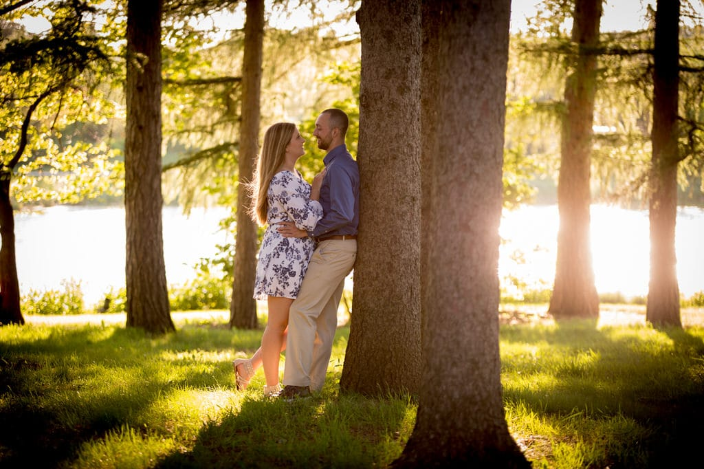 A newly engaged couple leans against a tree near a body of water. They stand in the grass and smile at each other.