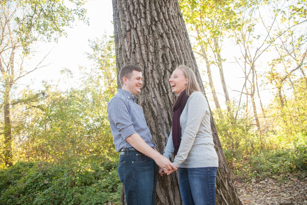 A newly engaged couple hold hands and laugh carelessly in front of a giant tree in the forest.