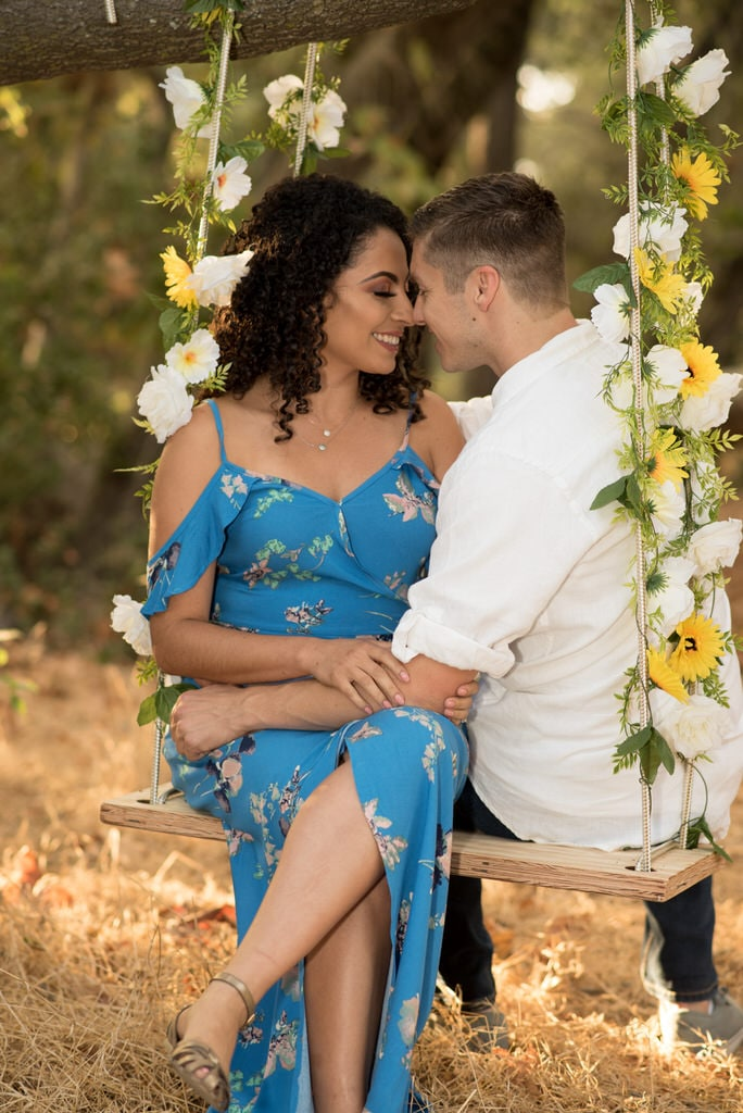 A recently engaged couple sit closely on a swing lined with fresh cut flowers. Their faces are close and they smile broadly and each other.