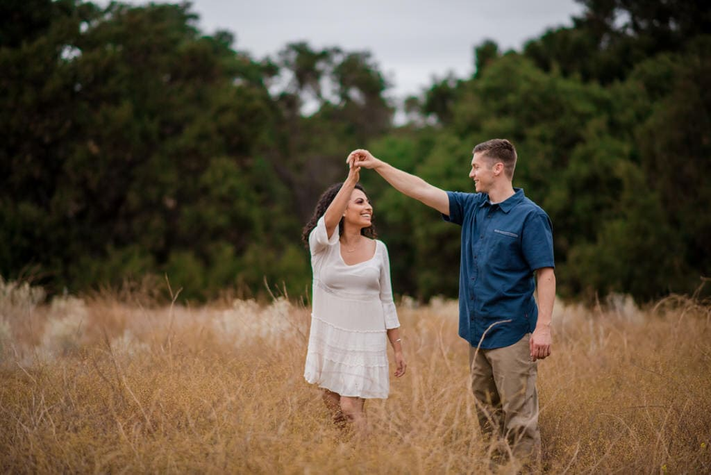 A man twirls his soon-to-be bride in the middle of a tall field surrounding by trees.