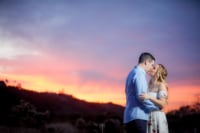 A young, newly engaged couple kiss sweetly as the sun sets in the background.