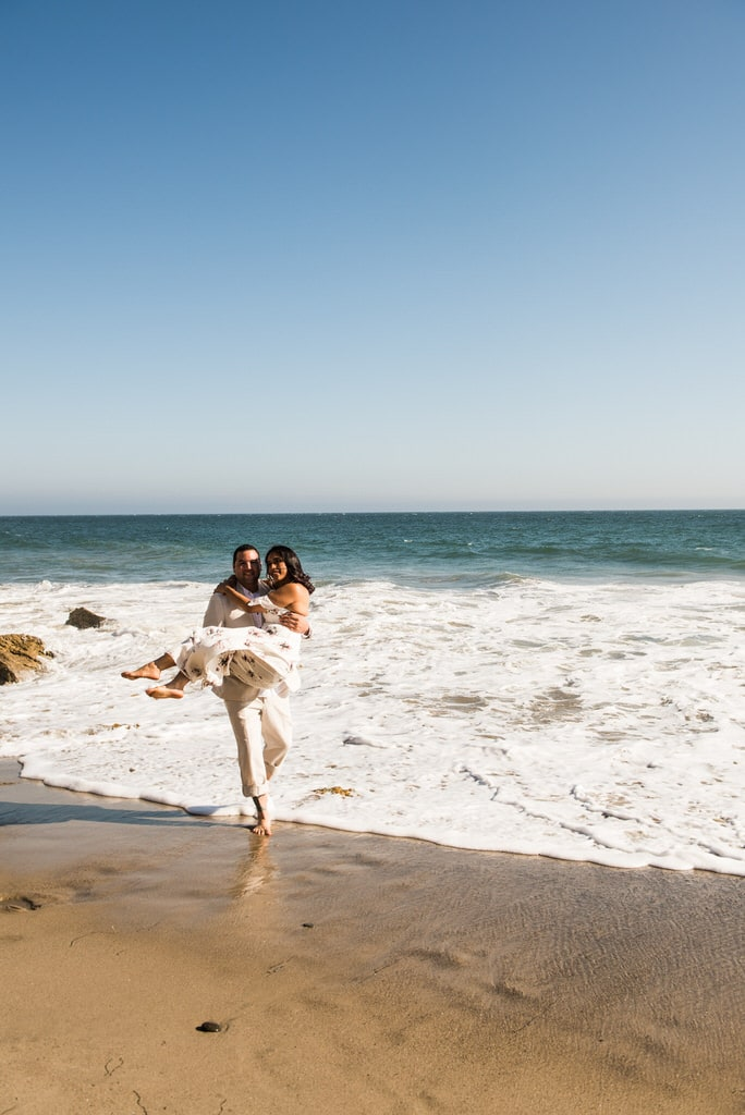 A man playfully carries his soon-to-be wife from the waters of the ocean.