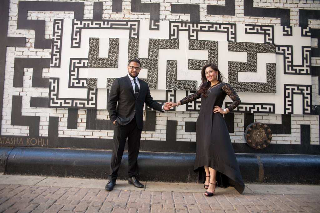 A newly engaged couple holding hands in front of a patterned wall outdoors.