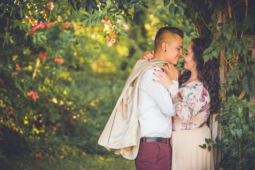 A hot latino couple goes in for a kiss underneath a coral hibiscus archway in the summer.