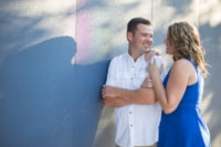 A couple looks at each other lovingly outdoors on a sunny day against a wall.