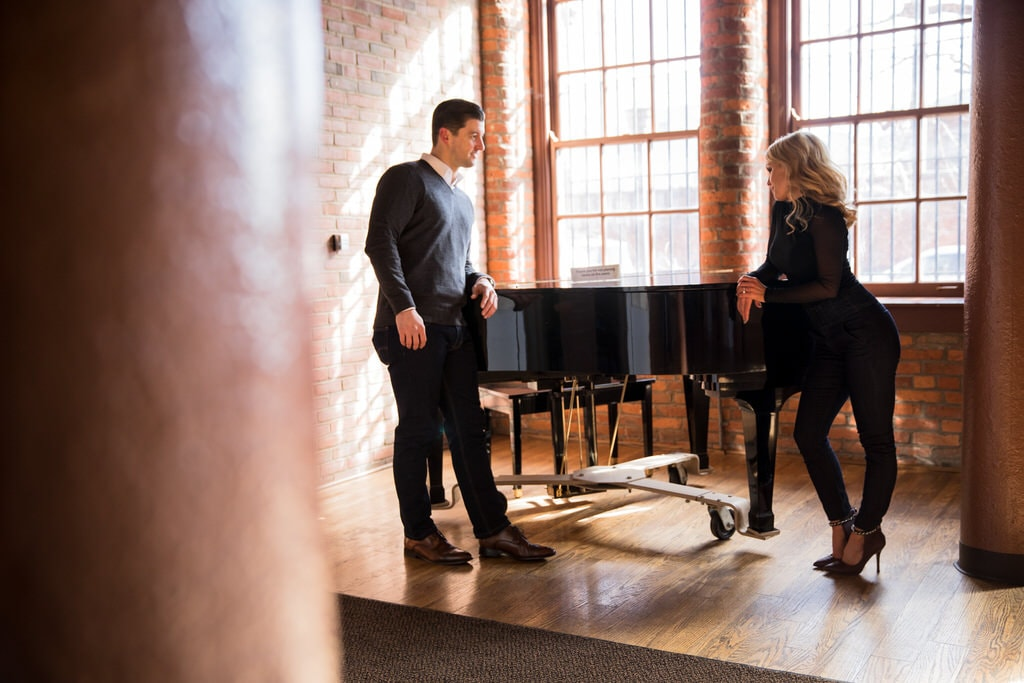 A stylish young couple shares a glance across a grand piano in an exposed brick loft with hardwood floors.