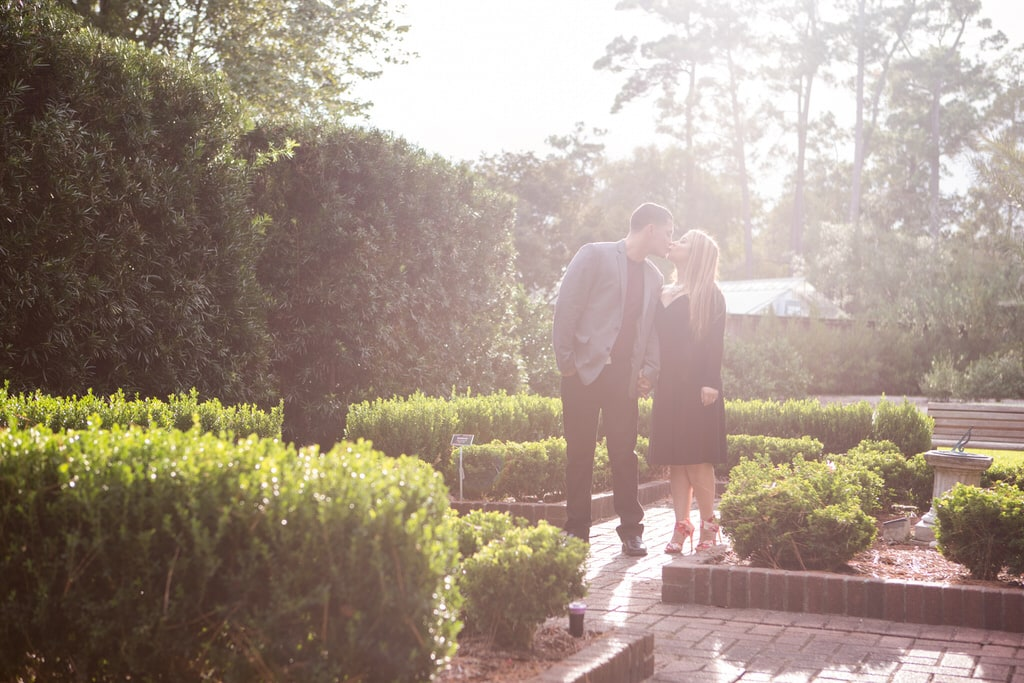 A young couple kiss in the garden on a beautiful sunny day.