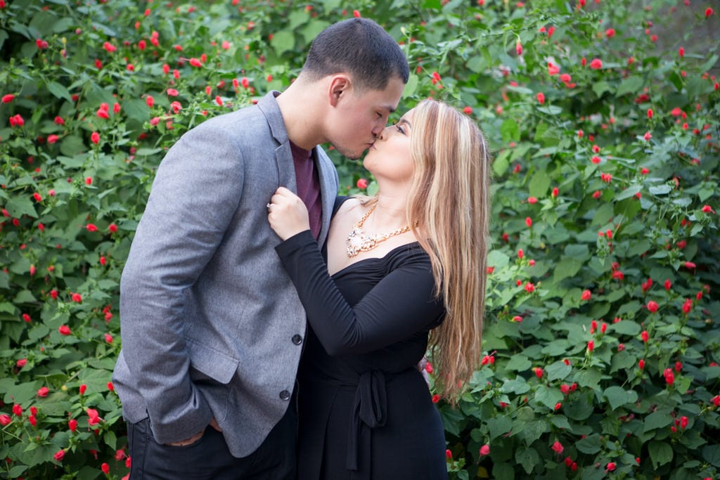 The young couple shares a firm kiss in front of high primrose bushes. The woman wears a classic black wrap dress with a statement necklace.