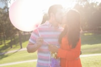 A young couple celebrates their engagement with balloons and streamers on a sunny day in the park.