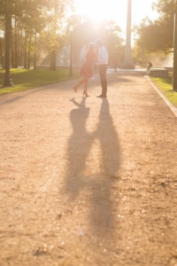 The beautiful sun is shining down on this couple as they demonstrate their love while walking along a gravel path. The sun radiating on this couple only gives this couple an eternal glow to develop their everlasting love.