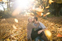 Bright yellow and orange leaves fall on the laughing couple as they begin to celebrate their love and soon-to-be solidified marriage. The fall colors truly make the couple glow exponentially which captures all of their love.