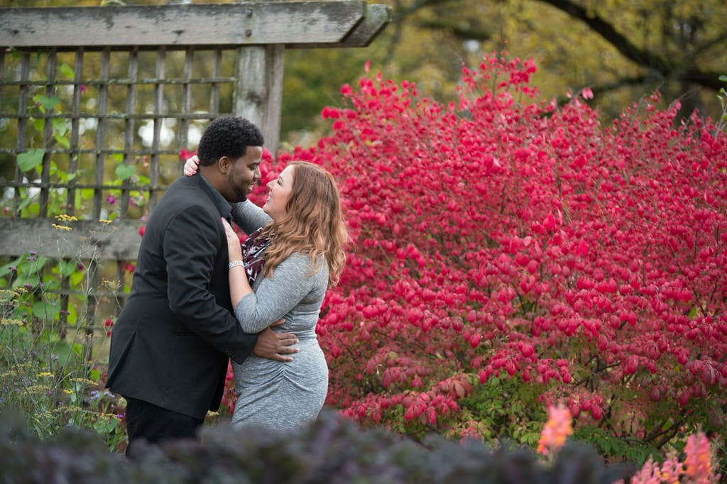 This couple holds one another while celebrating their fabulous engagement and time together while standing in front of a rustic wood garden wall and a beautiful vibrant bush.