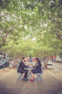 This couple sits at a bright blue set of tables and chairs while it is placed in the center of a very busy road. They hold hands and smile relentlessly because all they are sharing is their everlasting love. The red and blue in the scenery is complemented by the couple's looks, it makes this photograph more than pleasing to the eyes.