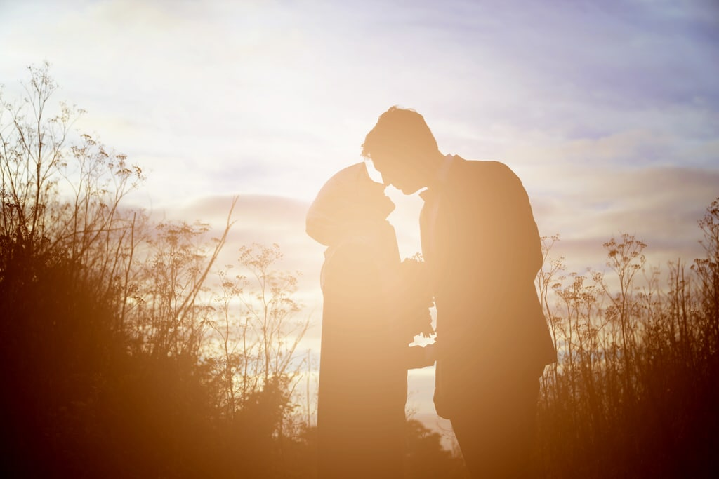 The photographer captures a beautiful silhouette of a young couple in a wildflower field.