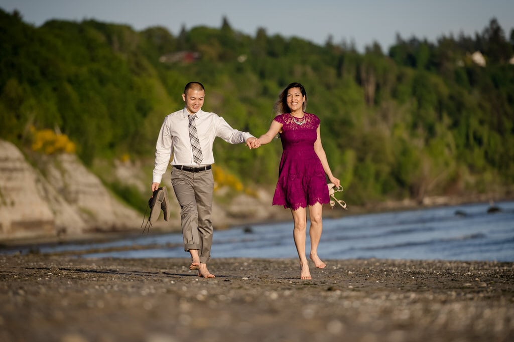 A light-hearted couple walks along the beach hand-in-hand as they smile at the photographer.
