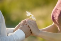 A couple holds a daisy between their hands and accent the diamond ring on her finger.